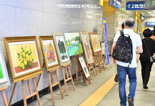 12일 오후 창원중앙역 대합실 통로에서 승객들이 오는 20일까지 열리는 동서양화 중견작가 작품전을 감상하고 있다./전강용 기자/