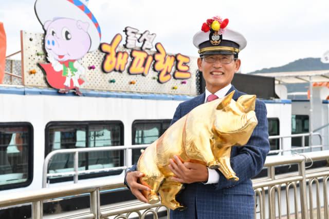 오용환 돝섬해피랜드 대표가 돝섬의 상징인 황금돼지를 안고 활짝 웃고 있다./전강용 기자/