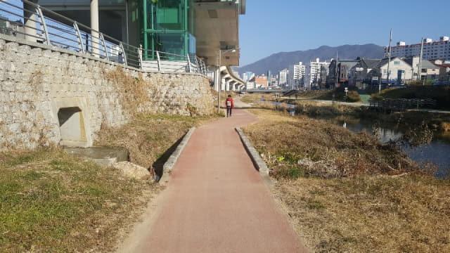 김해 해반천 산책로 개선 전(왼쪽) 모습과 안전 난간이 설치된 모습./김해시/