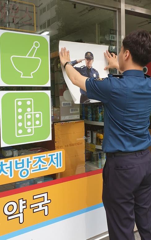 김해서부경찰서 경찰관이 관내 약국에 신장측정표와 경찰 포스터를 부착하고 있다./김해서부경찰서/