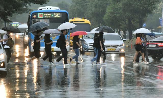 올해 첫 장맛비가 내린 26일 우산을 쓴 시민들이 창원시 의창구 은아아파트 사거리 횡단보도를 걷고 있다./전강용 기자/