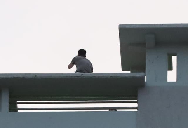 8일 오후 경남 거제시 옥포동 한 주상복합아파트 옥상에서 박모(45)씨가 경찰과 대치하고 있다. 박 씨는 이날 이 아파트 사무실 입주 한 업체 사장을 흉기로 찔러 숨지게 한 혐의를 받는다. 연합뉴스