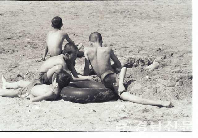 1960년대 후반 추정 가포 해수욕장에서 검은 고무 튜브를 베고 모래찜질을 즐기는 소년들의 모습