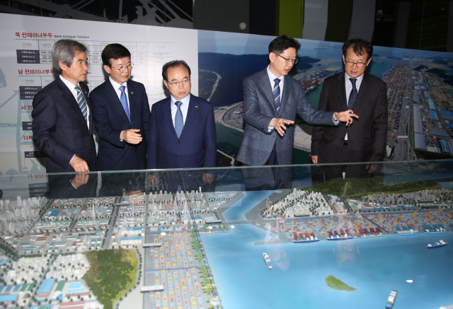 김경수(오른쪽 두 번째) 지사와 오거돈(오른쪽 세 번째) 부산시장이 지난 5월 3일 부산항 홍보관에서 '부산항 미래비전 실천을 위한 상생협약' 체결 후 홍보관을 둘러보고 있다./경남도/