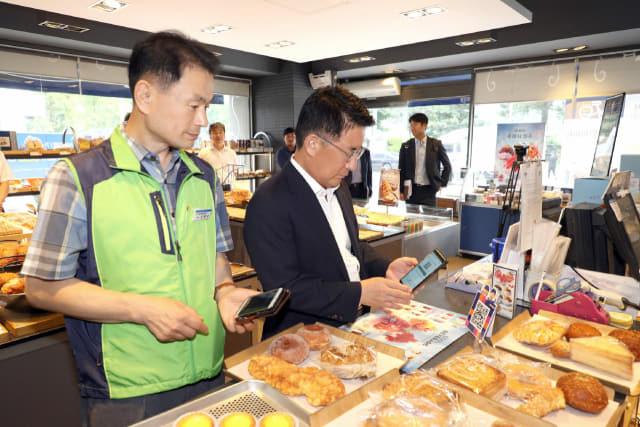 허만영(오른쪽) 창원시 제1부시장과 신현승 공무원노조 창원시지부장이 20일 오전 시청 인근 제과점에서 창원사랑 상품권으로 빵을 구입하고 결제하고 있다./창원시/