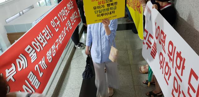 사천시 동지역 공립단설유치원 설립을 촉구하는 학부모들이 22일 사천시청 브리핑 룸 앞 복도에서 반대피켓을 들고 의사를 표명하고 있는 반대 시민들의 앞을 찬성 피켓을 든 채 지나가고 있다.허충호