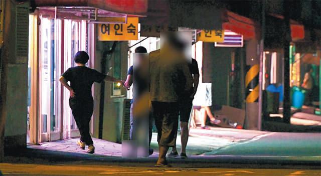 추석연휴 밤 창원시 마산합포구 서성동 성매매 집결지에서 한 업주가 남성의 손목을 잡아 당기고 있다./김승권 기자/
