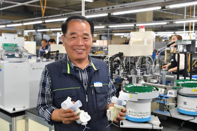 이장수 한국중천전화산업 대표이사가 지난 10일 마산자유무역지역 내 공장에서 생산된 세탁기 배수밸브 부품을 들어보이고 있다. /전강용 기자/