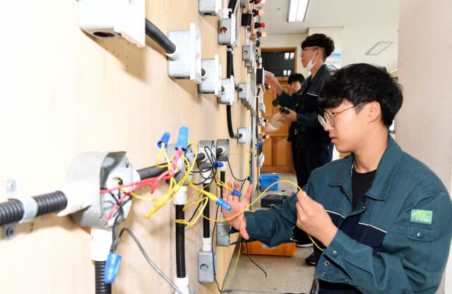 전기과 내선공사실에서 김용도 교사 지도로 3학년 남원지, 김경영, 한강민 학생이 옥내제어 실습을 하고 있다.