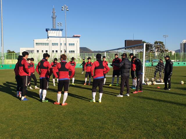경남FC 김종부 감독이 14일 함안운동장에서 선수들과 전술을 논의하고 있다.