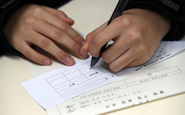 15일 오전 서울 서초고등학교에서 한 수험생이 2020학년도 대학수학능력시험 가채점표를 작성하고 있다. 연합뉴스