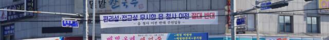 15일 함안군 칠원읍사무소 앞 상가 건물에 새 청사 이전 건립을 반대하는 플래카드가 붙여져 있다./김호철 기자/