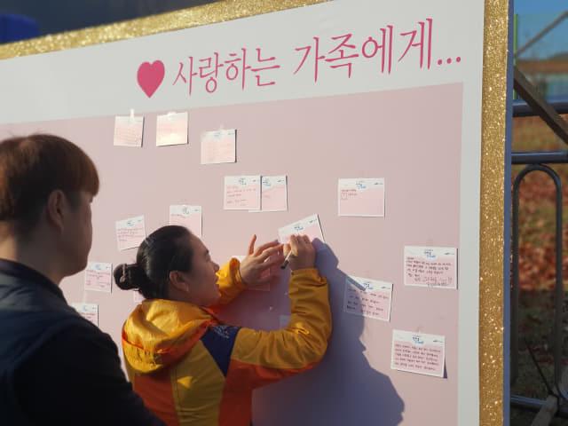 걷기대회에 참가한 임직원과 가족들이 가족들에게 바라는 점을 엽서에 써서 남기고 있다. /삼성중공업/