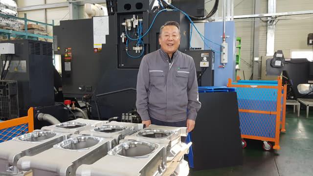 박성기 유진금속공업㈜ 대표이사가 지난 11일 김해시 주촌면 골든루트로 소재 공장에서 만든 진공펌프 부품 앞에서 활짝 웃고 있다.