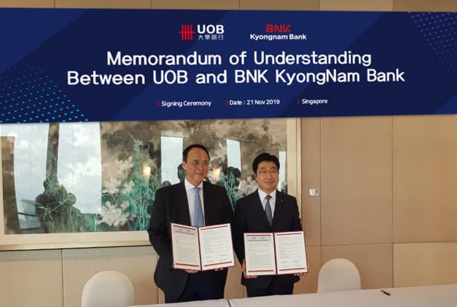 21일 BNK경남은행 황윤철(오른쪽) 은행장이 싱가포르 UOB은행 본사에서 상호협력강화를 위한 업무협약을 체결한 뒤 기념촬영을 하고 있다./BNK경남은행/
