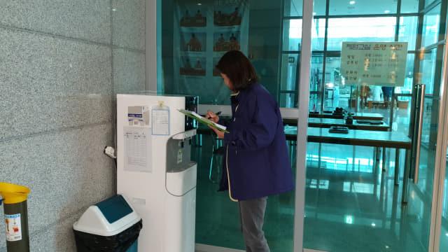 밀양시 직원이 다중이용시설에 설치된 정수기를 점검하고 있다.
