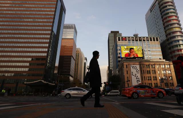 18일 정부가 내년부터 시행키로 한 50~299인 규모의 기업에 대한 주 52시간 근로제 적용을 한시적으로 유예키로 했다. 이날 오후 직장인으로 보이는 시민들이 해질녘 광화문네거리를 지나고 있다. 연합뉴스