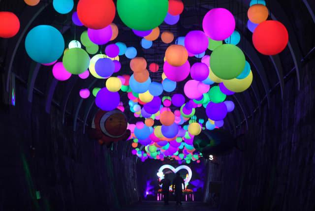 밀양 트윈터널을 찾은 관광객들이 색색의 등이 달린 '차원의 길'을 지나고 있다./김승권 기자/