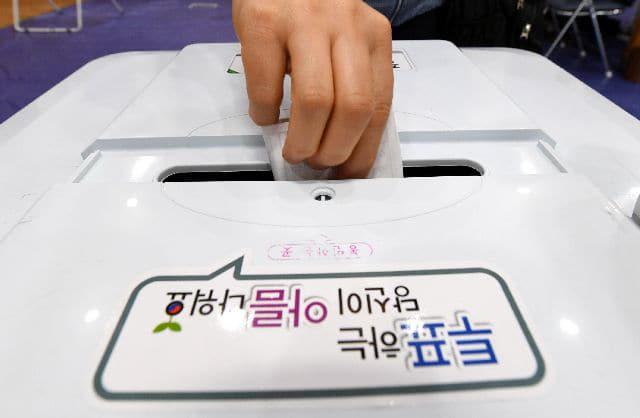 4일 오전 창원시 진해구 도천초등학교에 설치된 중앙동 사전투표소에서 한 시민이 투표함에 투표용지를 넣고 있다./김승권 기자/