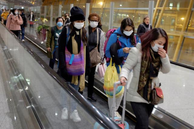 25일 중국 베이징 공항에 도착한 여행객들이 마스크를 쓴 채 에스컬레이터를 타고 이동하고 있다. 연합뉴스