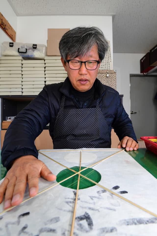 윤종민씨가 남해군 남해읍 야촌마을에 있는 자택에 마련한 연 공방 '사부랑공작소'에서 방패연을 만드는 과정을 보여주고 있다.