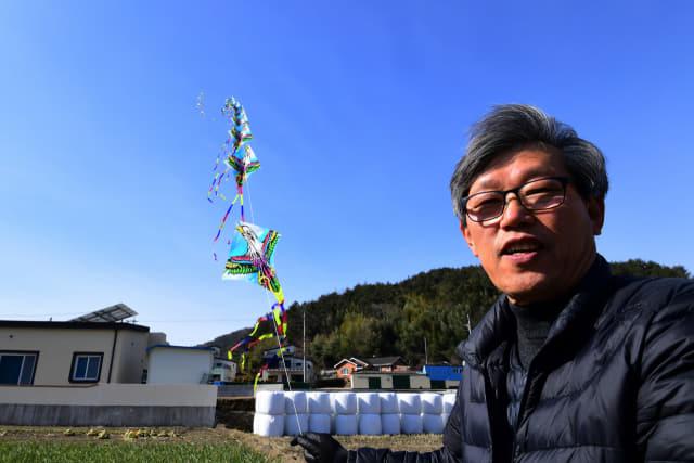 윤종민 씨가 자신의 연 공방 옆 들에서 3m 가격으로 120개를 연결해 길이 400m에 이르는 창작연을 날리고 있다.