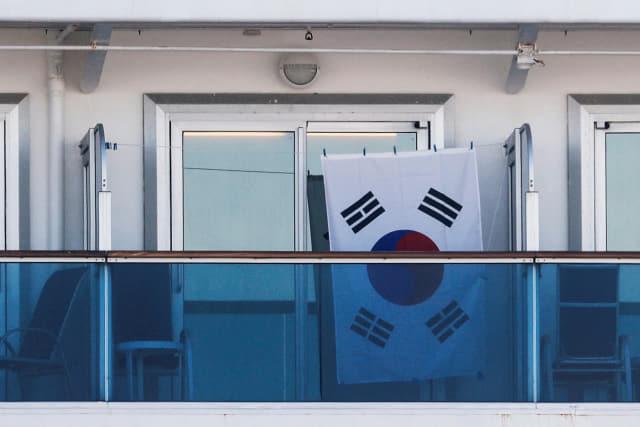 신종 코로나바이러스 감염증(코로나19) 환자가 집단 발생해 일본 요코하마 항에 발이 묶인 크루즈선 '다이아몬드 프린세스'호의 한 객실 발코니에 13일 태극기가 걸려 있다. 연합뉴스
