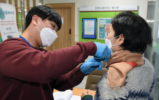 21일 오후 진주보건소 입구에서 직원이 내원자의 체온을 측정하고 있다./김승권 기자/