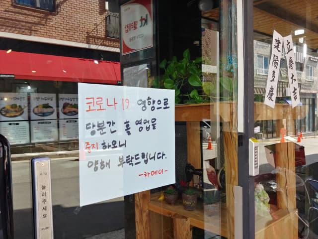 24일 김해시 율하천 카페거리의 한 식당 입구에 코로나19로 휴업한다는 글이 붙어 있다.