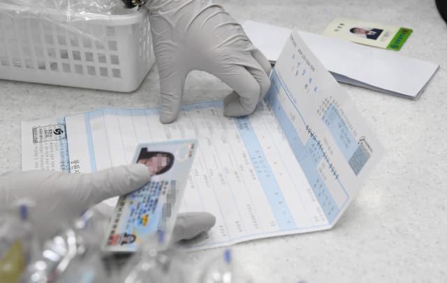 마스크 5부제가 시행된 9일 창원시의 한 약국에서 약사가 신분증, 주민등록등본, 학생증을 확인하고 있다./김승권 기자/ ★관련기사 6면
