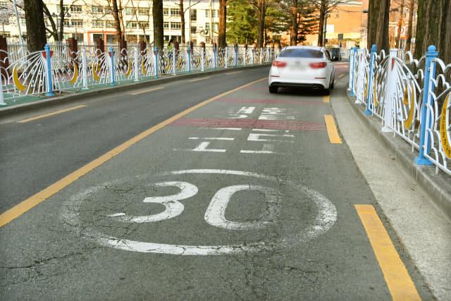 어린이 보호구역 교통사고를 엄벌하는 개정 도로교통법이 시행된 25일 창원시 의창구의 한 학교 앞 스쿨존의 노면에 규정속도 30㎞ 도색표시가 지워져 있다./전강용 기자/