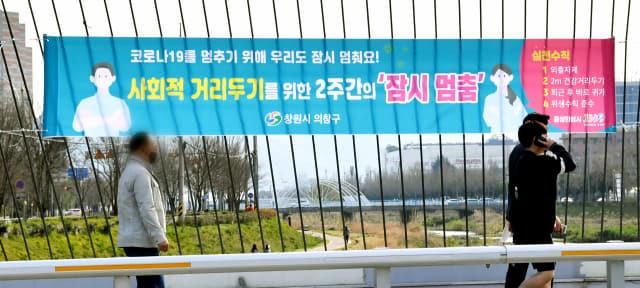 25일 창원시 의창구 창원천 3호교에 사회적 거리두기를 위한 2주간의 '잠시 멈춤' 플래카드가 내걸려 있다./전강용 기자/