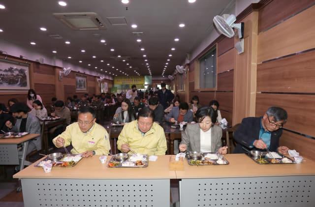 함안군청 구내식당에서 조근제 군수와 직원들이 한 방향을 보고 식사하고 있는 모습(왼쪽)과 의령군청 구내식당에 설치된 투명 칸막이 모습./함안군·의령군/
