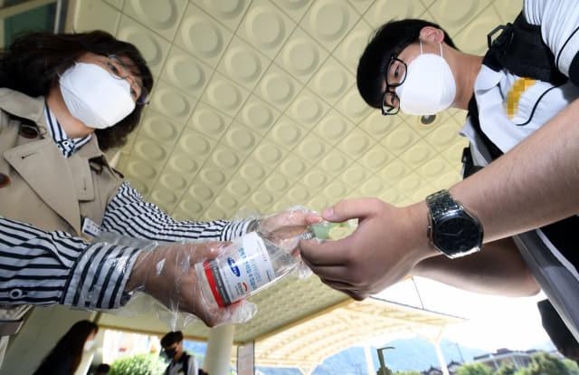 고3 등교개학 첫날인 20일 창원의 한 고등학교 현관에서 교사가 학생에게 손소독제를 뿌려주고 있다.