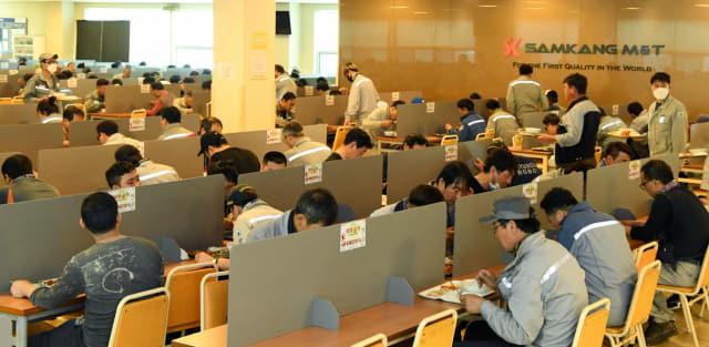 고성군 동해면 삼강엠앤티㈜ 직원들이 가림막이 설치된 식당에서 식사를 하고 있다./성승건 기자/