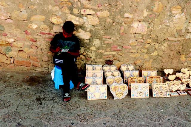 모스크 근처에 앉아 있는 모로코 아이.