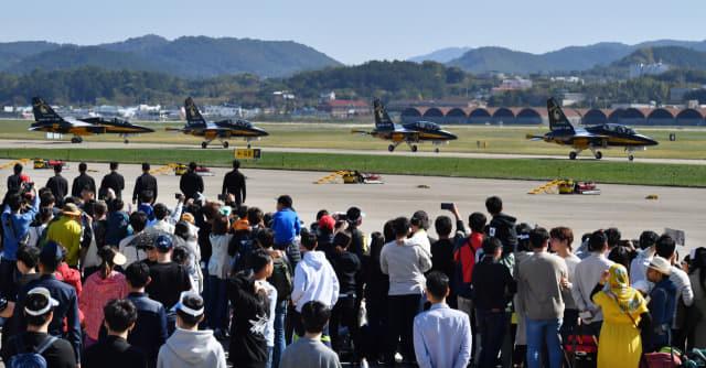 '2019 사천에어쇼'에서 관람객들이 공군 블랙이글스 특수비행팀의 T-50B 비행기가 활주로로 이동하는 장면을 보고 있다./경남신문DB/
