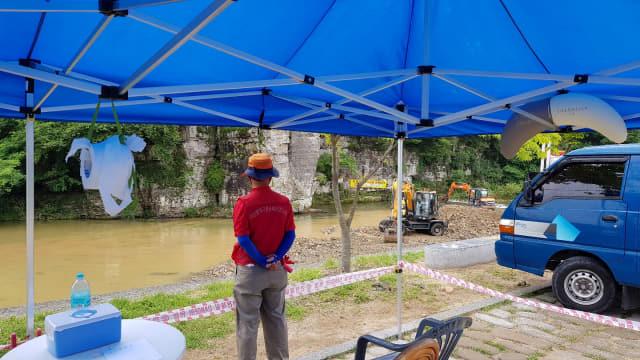 용대미 유원지의 안전요원이 초소 천막에서 구청의 평탄작업 공사를 지켜보고 있다.