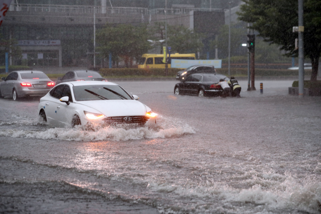 10일 호우경보가 내려진 부산 해운대구 센텀시티에서 갑자기 불어난 물에 승용차가 잠기는 등 물바다로 변하고 있다. 연합뉴스