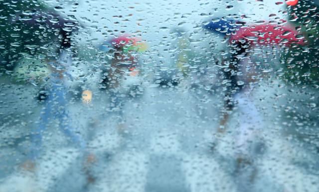 우산을 쓴 시민들이 창원 정우상가 앞 횡단보도를 건너고 있다./성승건 기자/
