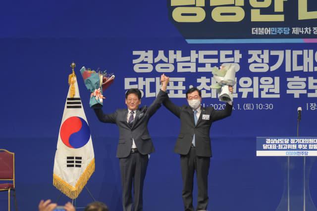 1일 창원컨벤션센터에서 열린 더불어민주당 경남도당 정기대의원대회에서 신임 도당위원장으로 선출된 김정호 의원과 전임 도당위원장인 민홍철 의원이 함께 손을 들어올리고 있다./민주당/