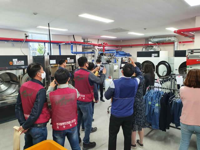 타 지역 지자체·기관 관계자들이 김해 노동자 작업복 세탁소를 찾은 모습./김해시/