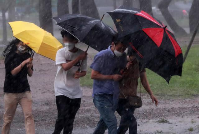 태풍 장미가 상륙한 10일 오후 부산 해운대 해수욕장 부근에서 시민들이 비바람을 피해 우산을 쓰고 걸어가고 있다. 연합뉴스