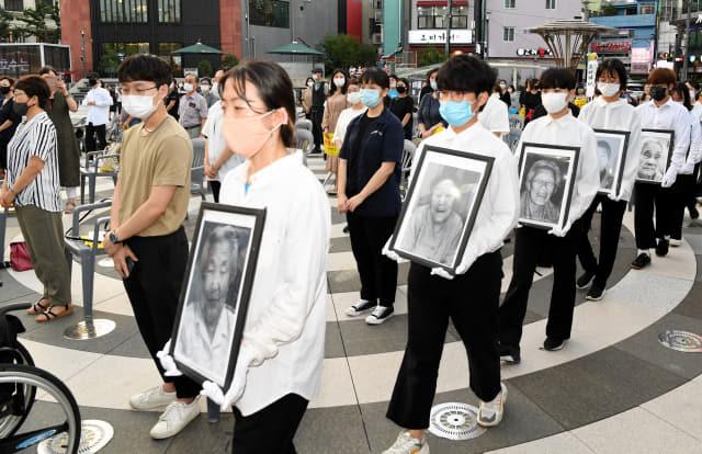 12일 오후 창원시 마산합포구 오동동 문화광장에서 열린 '2020 일본군 위안부 피해자 추모문화제'에서 참석자들이 위안부 피해자 할머니들의 영정사진을 들고 입장하고 있다./성승건 기자/