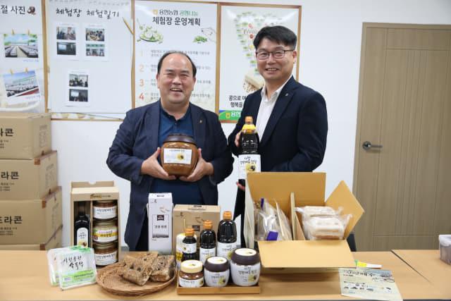 사천 용현농협 김정만 조합장(왼쪽)과 김창현 농협 사천시지부장이 용현농협이 생산한 콩 관련 식품들을 선보이고 있다./용현농협/