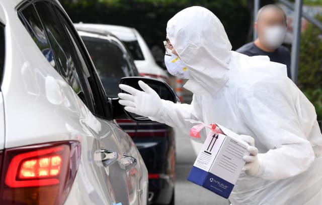 김해시 보건소 코로나 19 선별진료소에 의료진이 검체 채취를 받으려는 시민들을 안내하고 있다./김승권 기자/