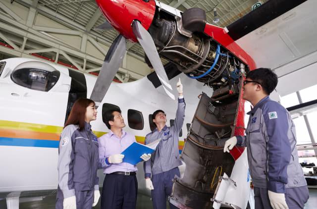 항공정비과 교수와 학생들이 실습용 항공기의 엔진 부분을 점검하고 있다.
