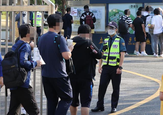 19일 오전 서울 시내 한 학교에 마련된 순경공채 필기시험장에서 응시생들이 수험표를 확인받은 뒤 입장하고 있다. 연합뉴스