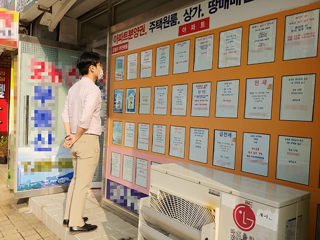 20일 오후 창원의 한 공인중개사 사무실 앞에서 시민이 매물 안내판을 살펴보고 있다.