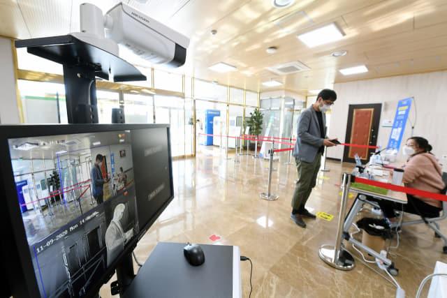 경남대표도서관 출입구에서 한 시민이 체온 측정 후 전자출입명부를 작성하고 있다.